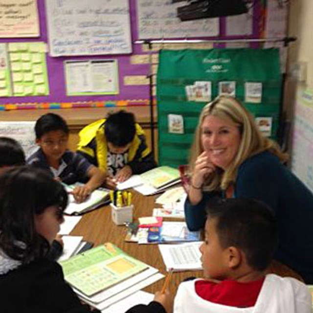 A Carrillo teacher helps her students with math problems.
