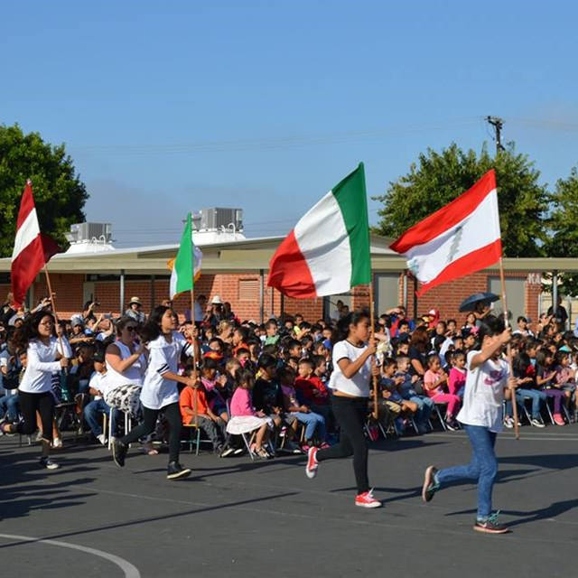 Students at Carrillo carry flags from other nations during the Day of Peace assembly.